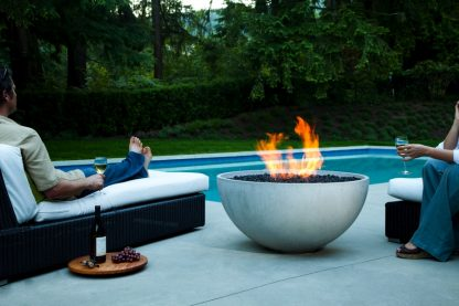 "Solus hemi 36"" fire pit with flames and couple relaxing near pool with wine and grapes"