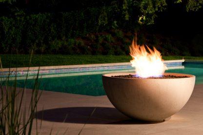 Solus hemi fire pit in halva colour, lit near green pool at dusk