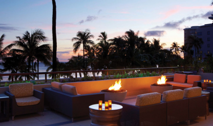 "Solus Hemi 36"" fire pits lit in portland colour on deck at Hyatt Regency Waikiki hotel overlooking sunset and water"