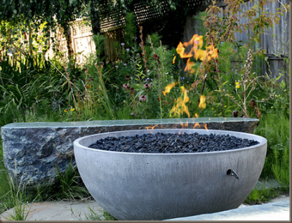 Solus hemi fire pit in garden, lit, with rough stone seating