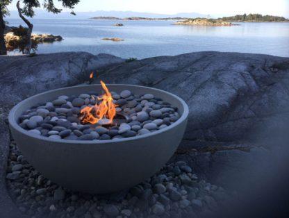 "Solus hemi 36"" fire pit in cinder colour lit on rocks overlooking ocean"